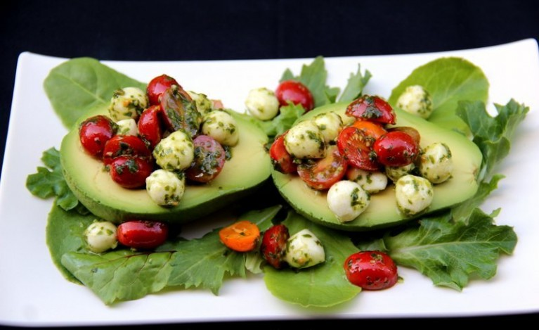 Use-a-spoon-to-fill-the-avocado-halves-with-the-caprese-filling