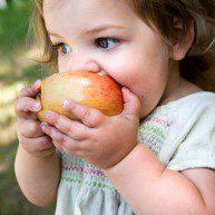 a dirty little girl eating a nice crispy apple