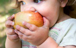 a dirty little girl eating a nice crispy apple